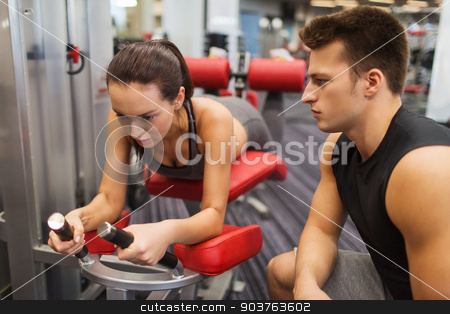 young woman with trainer exercising on gym machine stock photo, sport, fitness, lifestyle and people concept - young woman and personal trainer flexing leg muscles on gym machine by Syda Productions