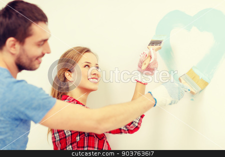 smiling couple painting small heart on wall stock photo, repair, building and home concept - smiling couple painting small heart on wall at home by Syda Productions