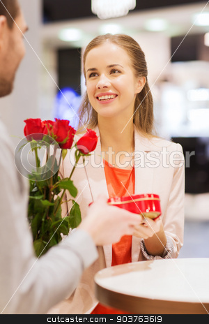 happy couple with present and flowers in mall stock photo, love, romance, valentines day, couple and people concept - happy young man with red flowers giving present to smiling woman at cafe in mall by Syda Productions