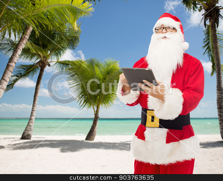 man in costume of santa claus with tablet pc stock photo, christmas, holidays, technology, travel and people concept - man in costume of santa claus with tablet pc computer over tropical beach background by Syda Productions