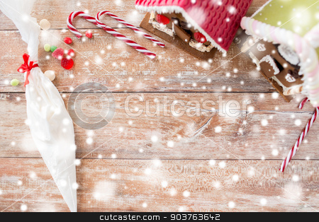 closeup of beautiful gingerbread houses on table stock photo, holidays, christmas, baking and sweets concept - closeup of beautiful gingerbread houses and glaze on blank table at home by Syda Productions