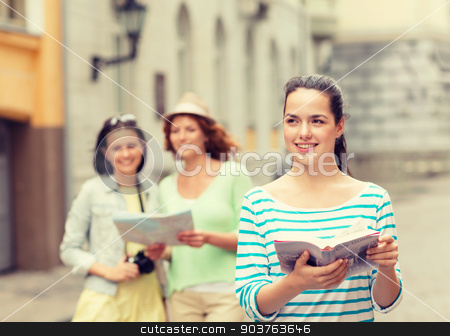 smiling teenage girls with city guides and camera stock photo, tourism, travel, leisure and holidays concept - smiling teenage girls with city guide, map and camera outdoors by Syda Productions