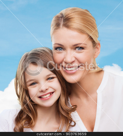 smiling mother and little girl stock photo, family, childhood, happiness and people - smiling mother and little girl over blue sky background by Syda Productions
