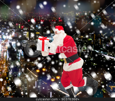 man in costume of santa claus with gift box stock photo, christmas, holidays and people concept - man in costume of santa claus running with gift box over snowy night city background by Syda Productions