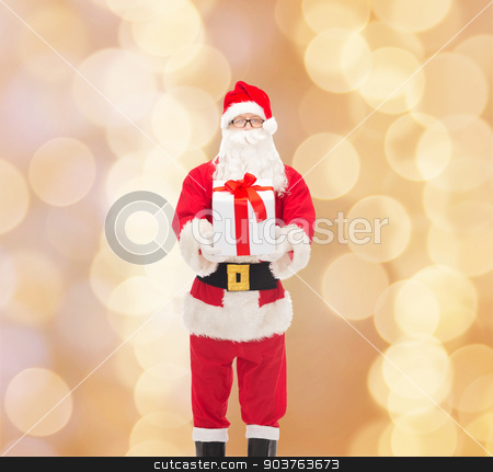 man in costume of santa claus with gift box stock photo, christmas, holidays and people concept - man in costume of santa claus with gift box over beige lights background by Syda Productions