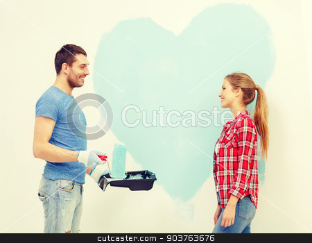 smiling couple painting big heart on wall stock photo, repair, building and home concept - smiling couple painting big heart on wall at home by Syda Productions