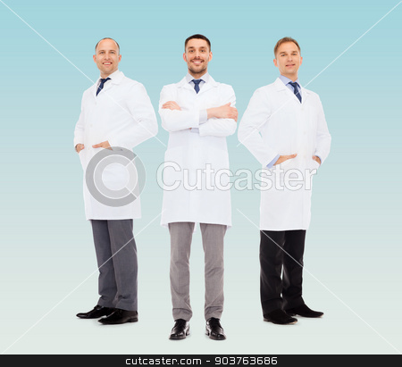 smiling male doctors in white coats stock photo, healthcare, profession and medicine concept - smiling male doctors in white coats over blue background by Syda Productions