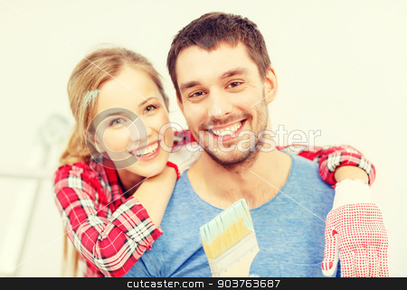 smiling couple covered with paint with paint brush stock photo, repair, building and home concept - smiling couple covered with paint with paint brush by Syda Productions