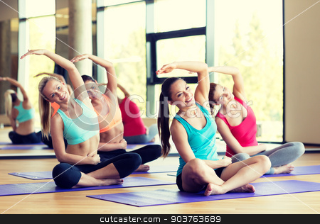 group of smiling women stretching in gym stock photo, fitness, sport, training and lifestyle concept - group of smiling women stretching in gym by Syda Productions