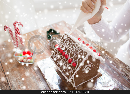close up of woman making gingerbread houses stock photo, cooking, people, christmas and decoration concept - close up of happy woman making gingerbread houses at home by Syda Productions