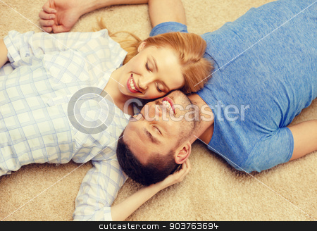 smiling happy couple lying on floor at home stock photo, love, family and happiness concept - smiling happy couple lying on floor at home by Syda Productions