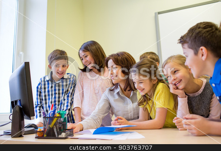 group of kids with teacher and computer at school stock photo, education, elementary school, learning, technology and people concept - group of school kids with teacher looking to computer monitor in classroom by Syda Productions