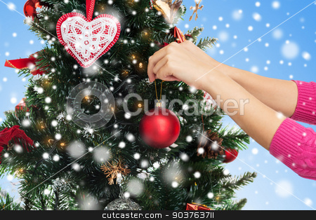 close up of hands with christmas tree decoration stock photo, winter holidays, celebration and people concept - close up of woman hands decorating christmas tree with ball over blue background with snow by Syda Productions
