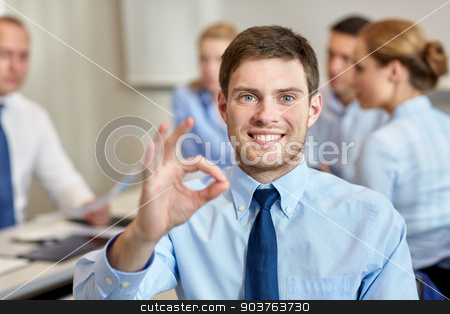group of smiling businesspeople meeting in office stock photo, business, people, gesture and teamwork concept - smiling businessman showing ok gesture with group of businesspeople meeting in office by Syda Productions