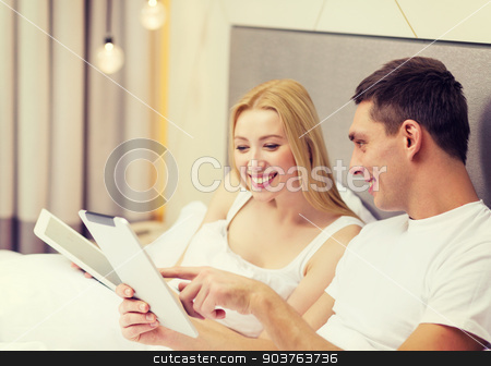 smiling couple in bed with tablet pc computers stock photo, hotel, travel, relationships, technology, intermet and happiness concept - smiling couple in bed with tablet computers by Syda Productions