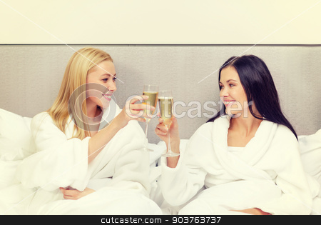 smiling girlfriends with champagne glasses in bed stock photo, hotel, travel, friendship and happiness concept - smiling girlfriends with champagne glasses in bed by Syda Productions