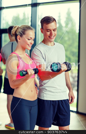 smiling young woman with personal trainer in gym stock photo, fitness, sport, exercising and diet concept - smiling young woman and personal trainer with dumbbells in gym by Syda Productions