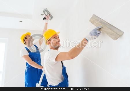 group of builders with tools indoors stock photo, business, building, teamwork and people concept - group of smiling builders in hardhats with plastering tools indoors by Syda Productions