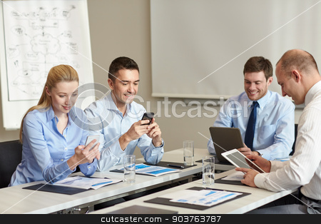 smiling business people with gadgets in office stock photo, business, people and technology concept - smiling business team with smartphone and papers meeting in office by Syda Productions
