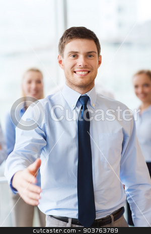 smiling businessman making handshake in office stock photo, business, people and teamwork concept - smiling businessman making handshake gesture with group of businesspeople in office by Syda Productions