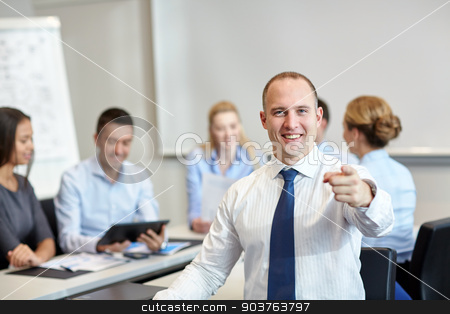 group of smiling businesspeople meeting in office stock photo, business, people, gesture and teamwork concept - smiling businessman pointing finger to you with group of businesspeople meeting in office by Syda Productions