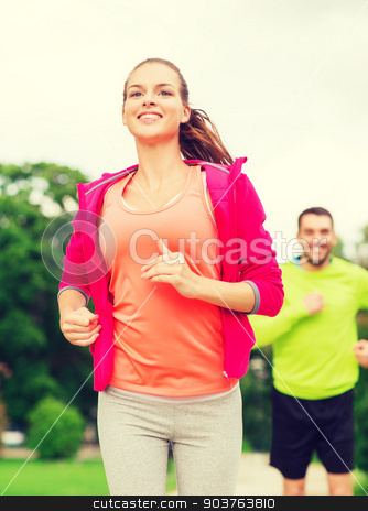 smiling couple running outdoors stock photo, fitness, sport, friendship and lifestyle concept - smiling couple running outdoors by Syda Productions
