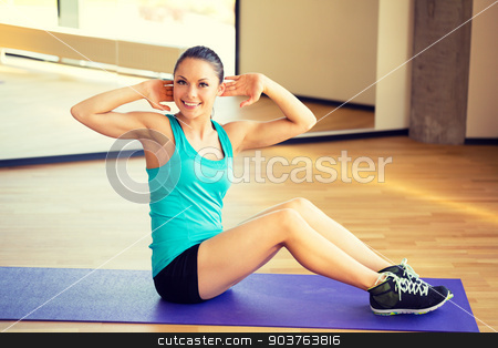 smiling woman doing exercises on mat in gym stock photo, fitness, sport, training and lifestyle concept - smiling woman doing exercises on mat in gym by Syda Productions