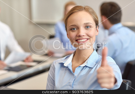 group of smiling businesspeople meeting in office stock photo, business, people, gesture and teamwork concept - smiling businesswoman showing thumbs up with group of businesspeople meeting in office by Syda Productions