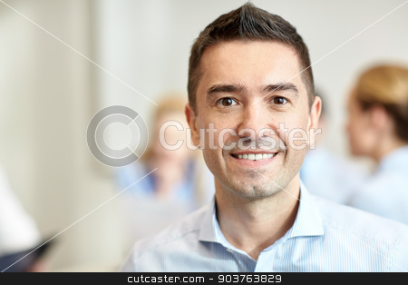 smiling businessman face in office stock photo, business, people and teamwork concept - smiling businessman with group of businesspeople meeting in office by Syda Productions