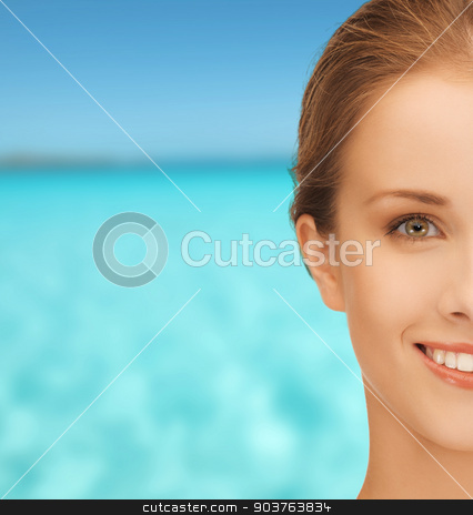 beautiful young woman over blue sky and sea stock photo, people and beauty concept - beautiful young woman over blue sky and sea background by Syda Productions
