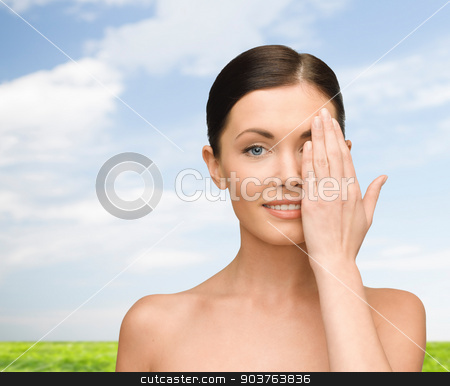 smiling young woman covering face with hand stock photo, beauty, people and health concept - smiling young woman covering half of face with hand over blue sky and grass background by Syda Productions