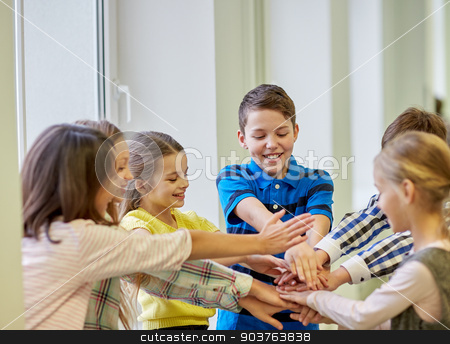 group of smiling school kids putting hands on top stock photo, education, elementary school, children, break and people concept - group of smiling school kids putting hands on top in corridor by Syda Productions