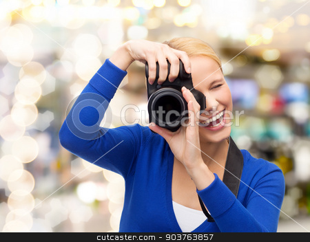 smiling woman taking picture with digital camera stock photo, photography, technology, holidays, and people concept - smiling young woman taking picture with digital camera over lights background by Syda Productions