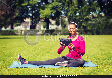 smiling woman with tablet pc outdoors stock photo, fitness, park, technology and sport concept - smiling african american woman with tablet pc computer and headphones on mat outdoors by Syda Productions