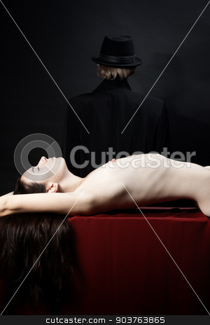victim of a vampire stock photo, beautiful young nude girl lying on the red fabric. In the background is the person in a black hat and cloak by Suchota