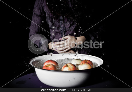Apple bobbing stock photo, young girl in a purple blouse plays apple bobbing by Suchota