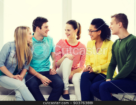five smiling teenagers having fun at home stock photo, education, leisure and happiness concept - five smiling teenagers having fun at home or school by Syda Productions