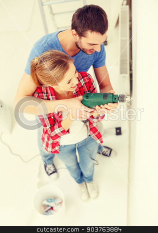 smiling couple drilling hole in wall at home stock photo, repair, interior design, building, renovation and home concept - smiling couple drilling hole in wall at home by Syda Productions
