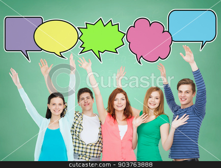 group of smiling teenagers with text bubbles stock photo, school, education, communication, gesture and people concept - group of smiling teenagers waving hands over green board background with text bubbles by Syda Productions
