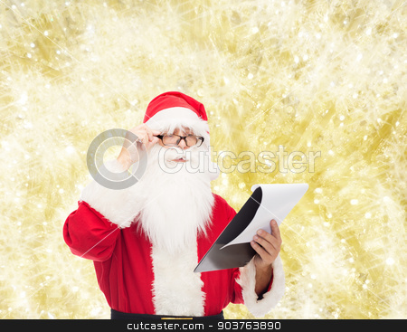 man in costume of santa claus with notepad stock photo, christmas, holidays and people concept - man in costume of santa claus with notepad over yellow lights background by Syda Productions
