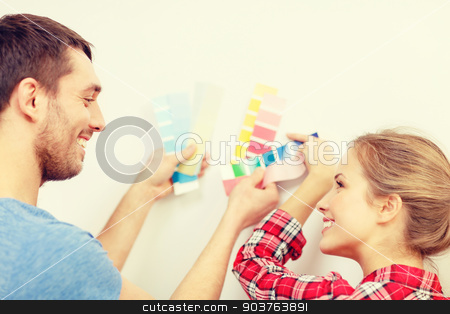 smiling couple looking at color samples at home stock photo, repair, interior design, building, renovation and home concept - smiling couple looking at color samples at home by Syda Productions