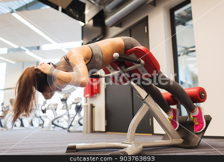 young woman flexing back muscles on bench in gym stock photo, sport, training, fitness, lifestyle and people concept - young woman flexing back and abdominal muscles on bench in gym by Syda Productions