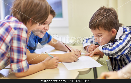 group of schoolboys writing or drawing at school stock photo, education, elementary school, learning and people concept - group of schoolboys with pens and papers writing or drawing in classroom by Syda Productions