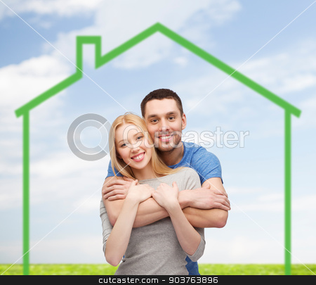 smiling couple hugging over green house stock photo, love, home, people and family concept - smiling couple hugging over green house and blue sky with grass background by Syda Productions