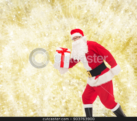 man in costume of santa claus with gift box stock photo, christmas, holidays and people concept - man in costume of santa claus running with gift box over yellow lights background by Syda Productions
