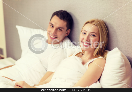 happy couple sleeping in bed stock photo, hotel, travel, relationships, and happiness concept - happy couple in bed by Syda Productions