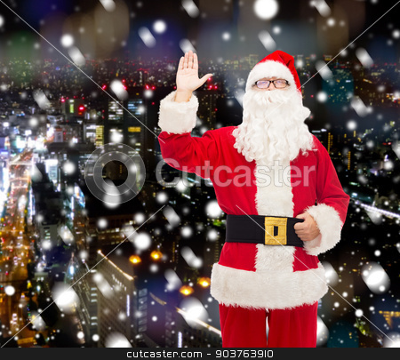 man in costume of santa claus stock photo, christmas, holidays, gesture and people concept - man in costume of santa claus waving hand over snowy night city background by Syda Productions