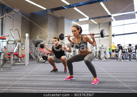 young man and woman training with barbell in gym stock photo, sport, bodybuilding, lifestyle and people concept - young man and woman with barbell flexing muscles and making shoulder press squat in gym by Syda Productions