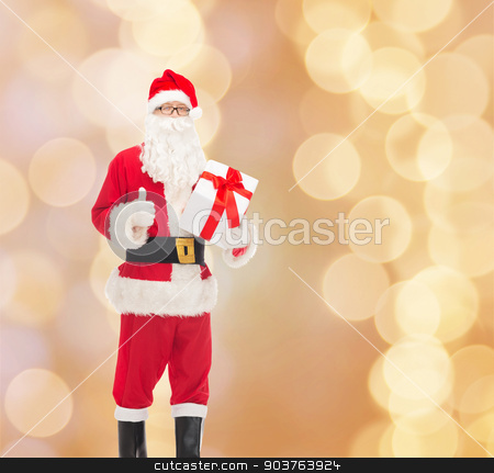 man in costume of santa claus with gift box stock photo, christmas, holidays and people concept - man in costume of santa claus with gift box showing thumbs up gesture over beige lights background by Syda Productions