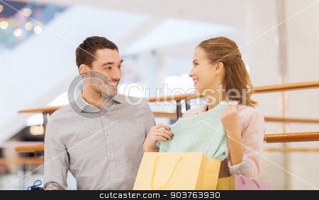 happy young couple with shopping bags in mall stock photo, sale, consumerism and people concept - happy young couple showing content of shopping bags in mall by Syda Productions